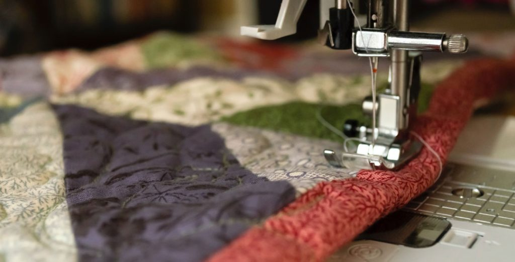 photo of sewing machine footer stitching a quilt by jeff wade