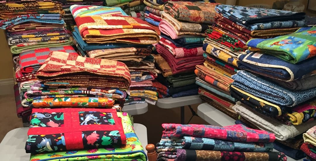 photo of stacks of charity quilts made for canada 150