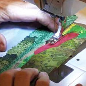 photo of a fabric postcard being sewn